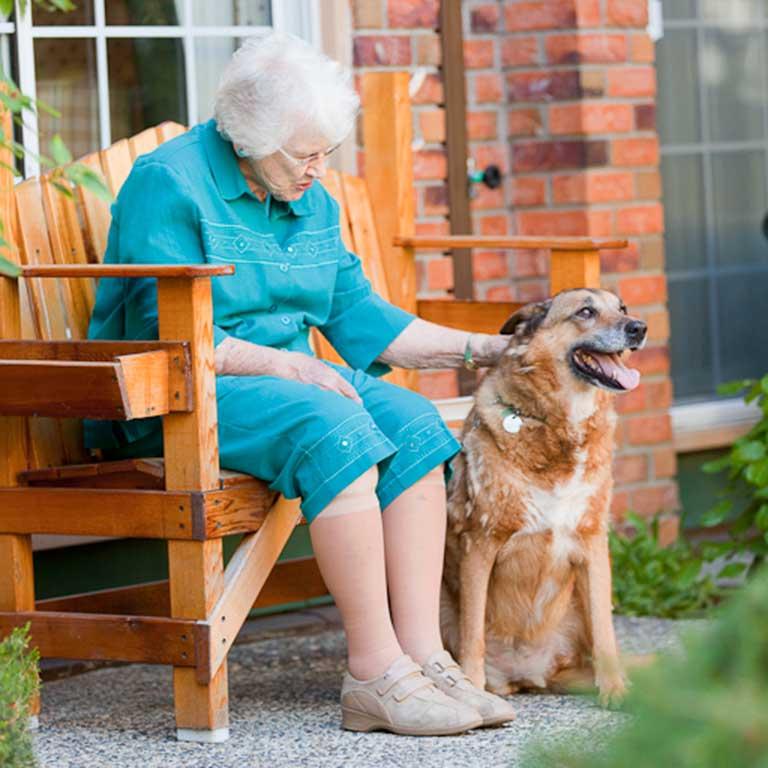 VRS Sunnyside Manor Seniors Community Our Mission happy senior resident with dog in garden